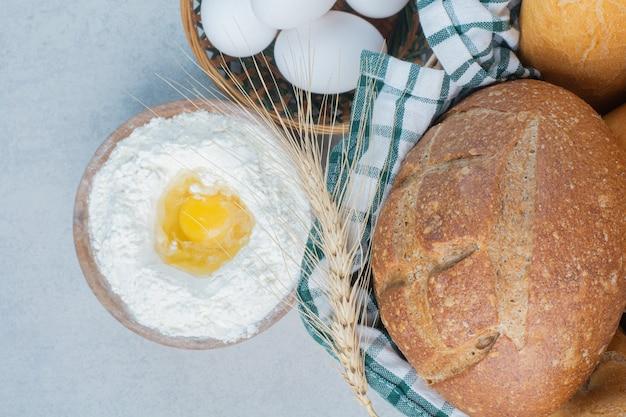 Cestino di pane vario insieme a farina e uova. foto di alta qualità