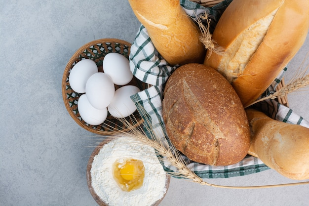 Basket of various bread together with flour and eggs. high quality photo