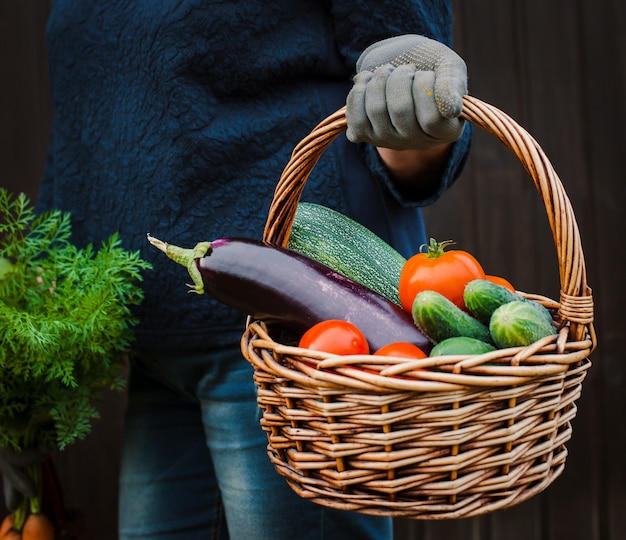 Basket of vegetables in the hands of a farmer on a wooden.