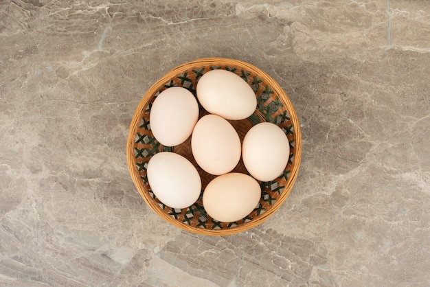 Basket of white eggs on marble table .