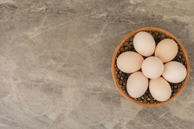 Cesto di uova bianche sul tavolo di marmo.