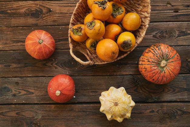 Корзина с урожаем хурмы и тыквы на деревянном столе