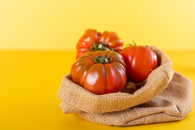 赤い家宝のトマトと黄色の背景のバスケット