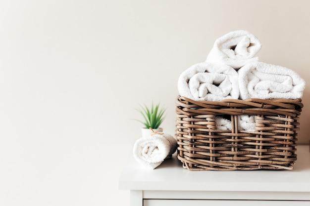 Корзина с аксессуарами для ванной. набор свернутых и сложенных полотенец. концепция уборки отеля