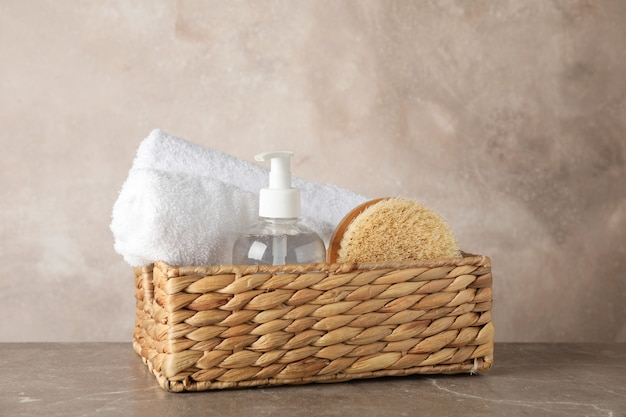 Basket with body care accessories on grey background, space for text
