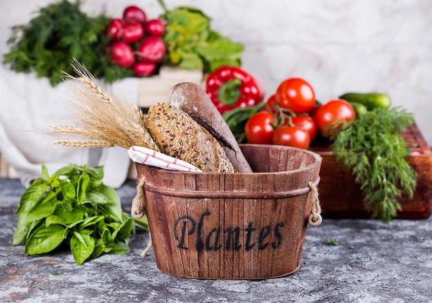Корзина с хлебом и овощами на большом столе