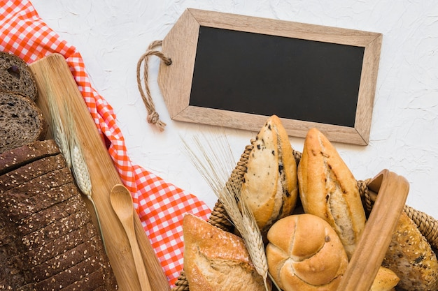 Basket with buns near bread and blackboard
