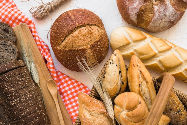Basket with buns near loaves of bread