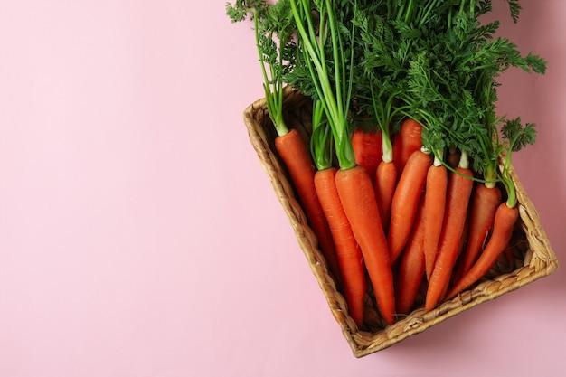 Корзина с морковью на розовом фоне, вид сверху