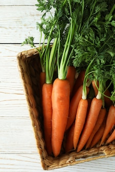 Basket with carrot on white wooden table