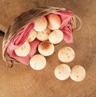 素朴な木の表面にチーズ パンを入れた市松模様の布のバスケット