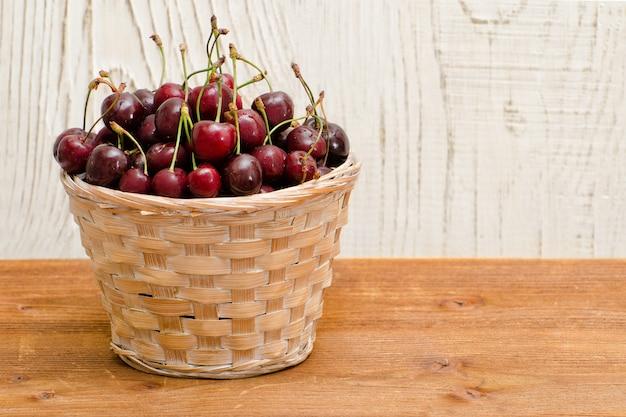 Корзина с вишнями на деревянном столе, пустое место