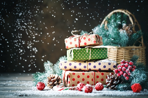 Basket with christmas toys and christmas gifts on a wooden background