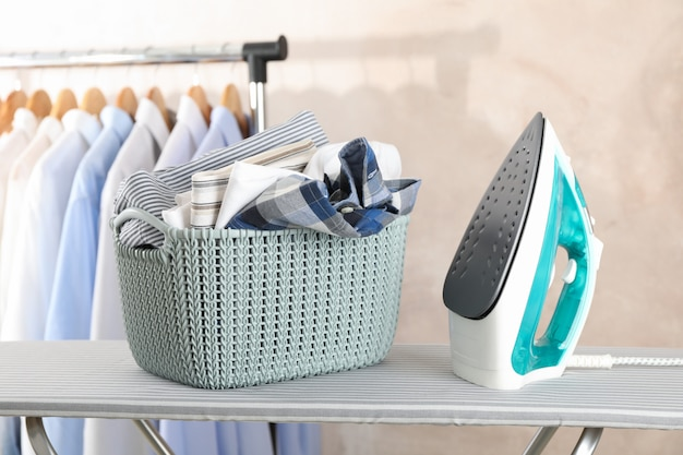 Basket with clean laundry and iron on ironing board,