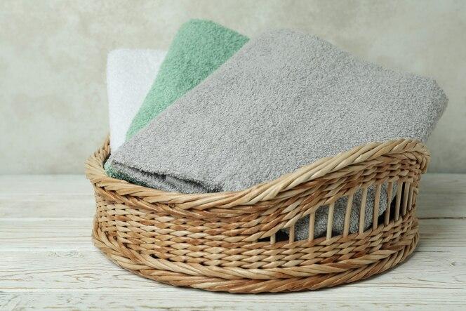 cestino con asciugamani puliti sulla tavola di legno bianca