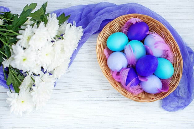 Basket with colored eggs on a wooden background. concept happy easter.