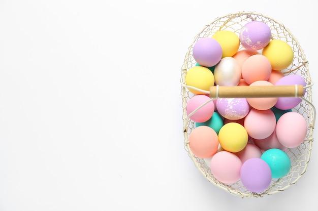 Корзина с красочными пасхальными яйцами на белом