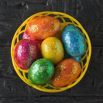 Корзина с разноцветными яйцами на черном столе