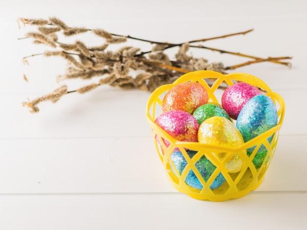 Корзина с красочными яйцами на белом деревенском столе