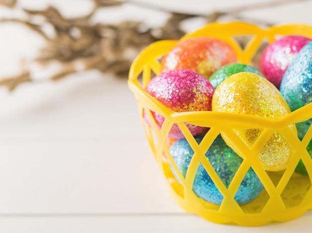 Корзина с разноцветными яйцами на белом деревянном столе