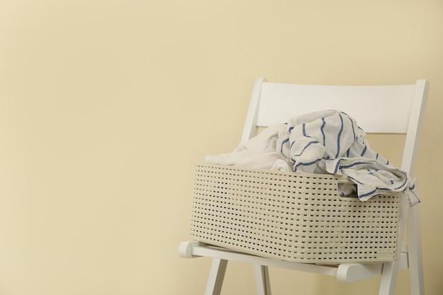 木製の椅子にしわくちゃの服のバスケット