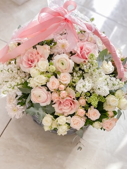 A basket with delicate colors. roses, ranunculi, lilacs. spring bouquet as a gift to your beloved. beautiful floral arrangement