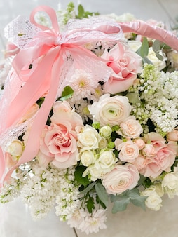A basket with delicate colors. roses, ranunculi, lilacs. spring bouquet as a gift to your beloved. beautiful romantic floral arrangement.