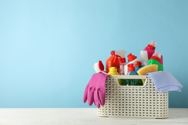 Basket with detergent and cleaning supplies on blue background, space for text