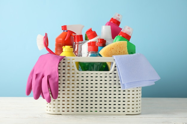 Basket with detergent and cleaning supplies on blue, close up