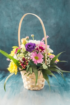 Basket with different flowers placed on desk