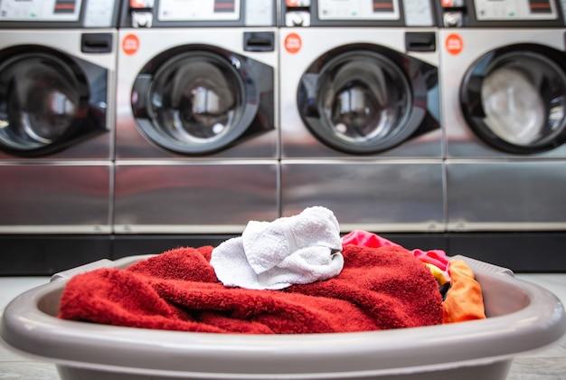 汚れた服や洗濯機のある洗濯室の洗濯物が入ったバスケット