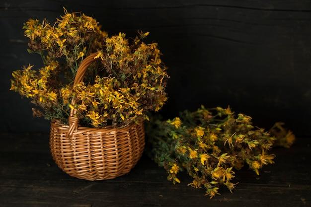 暗い木製の背景に乾燥したセントジョンズワートグラスと新鮮な草のバスケット
