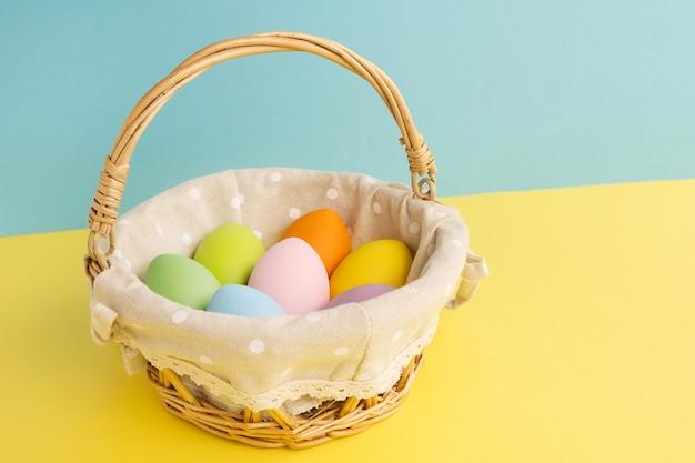 黄青色の背景にイースターカラフルな卵とバスケット。ハッピーイースターのコンセプト Premium写真