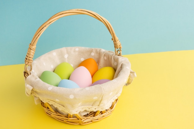 Basket with easter colorful eggs on yellow blue background. happy easter concept