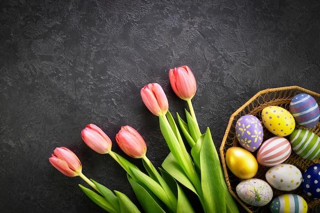 Корзина с пасхальными яйцами и розовыми тюльпанами на темном бетонном фоне