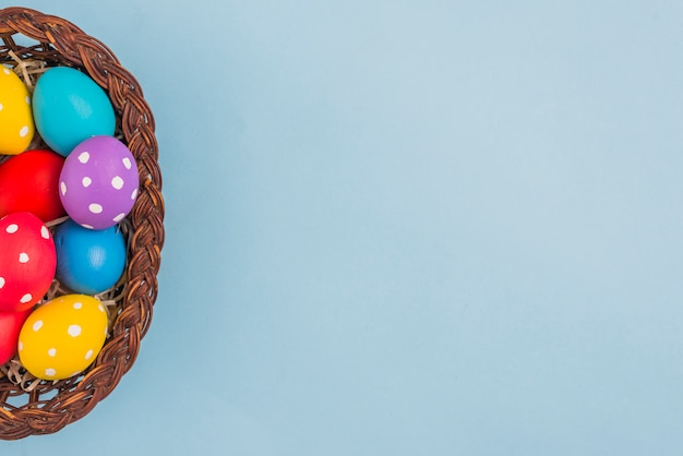Basket with easter eggs on blue table