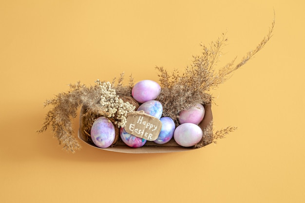 Basket with easter eggs on a colored isolated wall