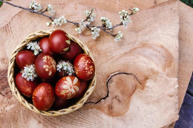 소박한 나무 테이블에 빨간 부활절 달걀 바구니