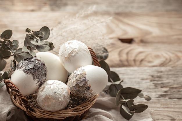 Корзина с яйцами и сушеными цветами на размытом фоне. оригинальная идея для украшения пасхальных яиц.
