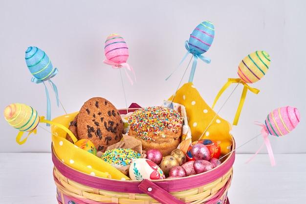 계란과 부활절 케이크 바구니입니다. 다채로운 계란과 휴일 케이크.