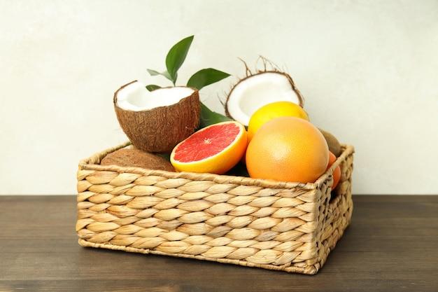 Корзина с экзотическими фруктами на деревянном столе.
