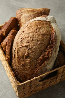 Basket with fresh bread on gray table