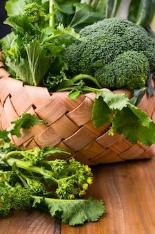 木製の背景に新鮮な緑の野菜のバスケット。アボカド、ブロッコリー、cime di rapaその他の野菜。テキスト用の空き容量。コピースペース。