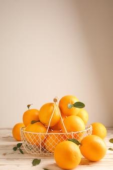 Корзина со свежими апельсинами на белом столе