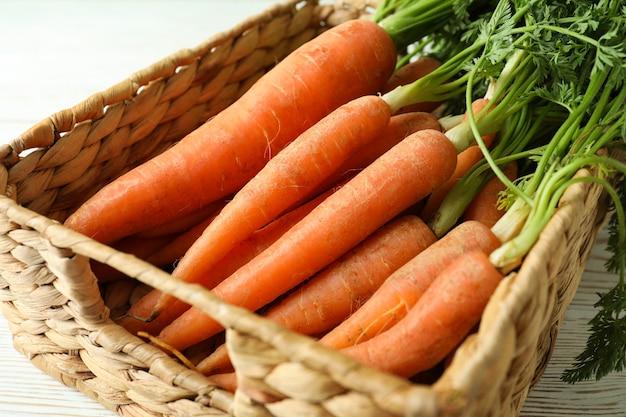 Корзина со свежей спелой морковью, крупным планом