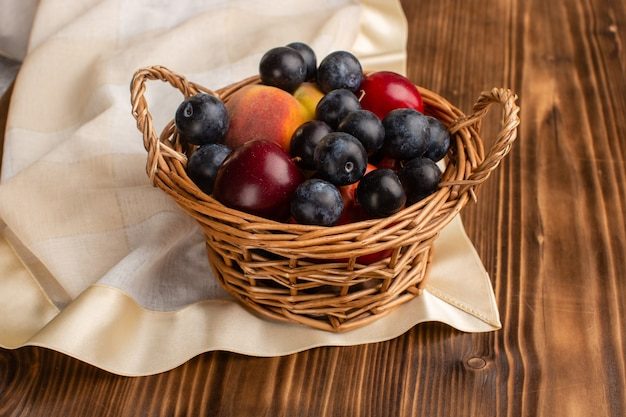Basket with frutis blackthorns plums and peaches on wood