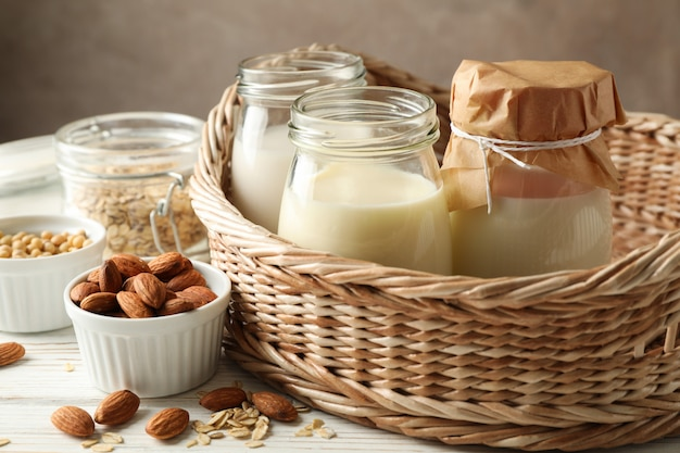 Basket with a glasses of different types milk on wooden