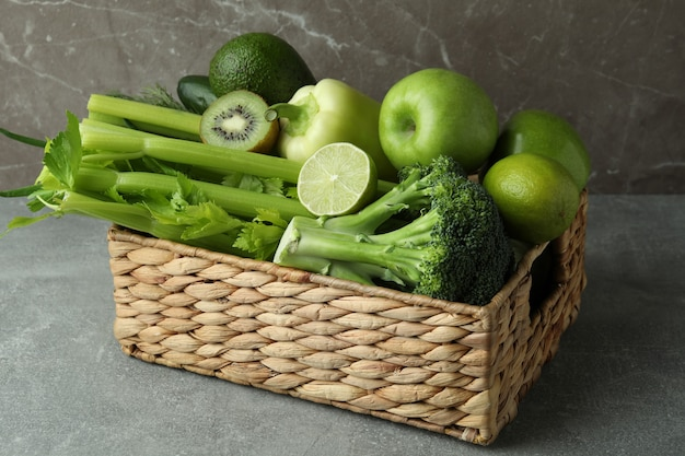灰色のテーブルに緑の野菜とバスケット