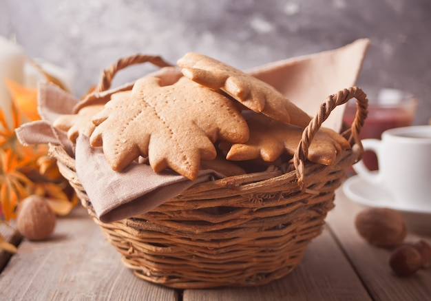 Basket with homemade cookies, cuop of coffee, leaves on the wooden table. autumn harvest. autumn concept. top view.