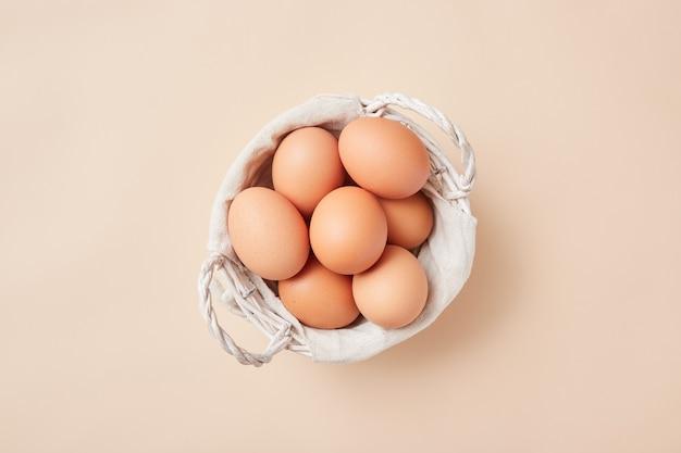 Корзина с домашними яйцами по центру картинки на бежевом фоне